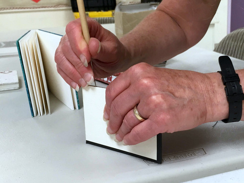 Jill Abilock demonstrating how to punch cover holes for coptic binding